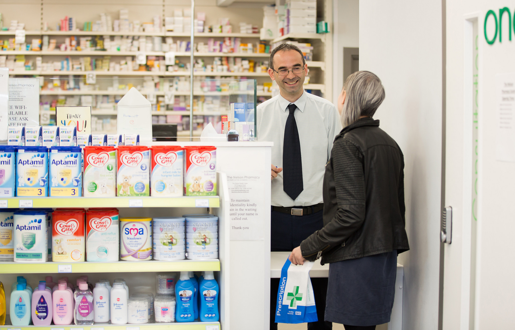 Woman collecting her prescription from a pharmacy