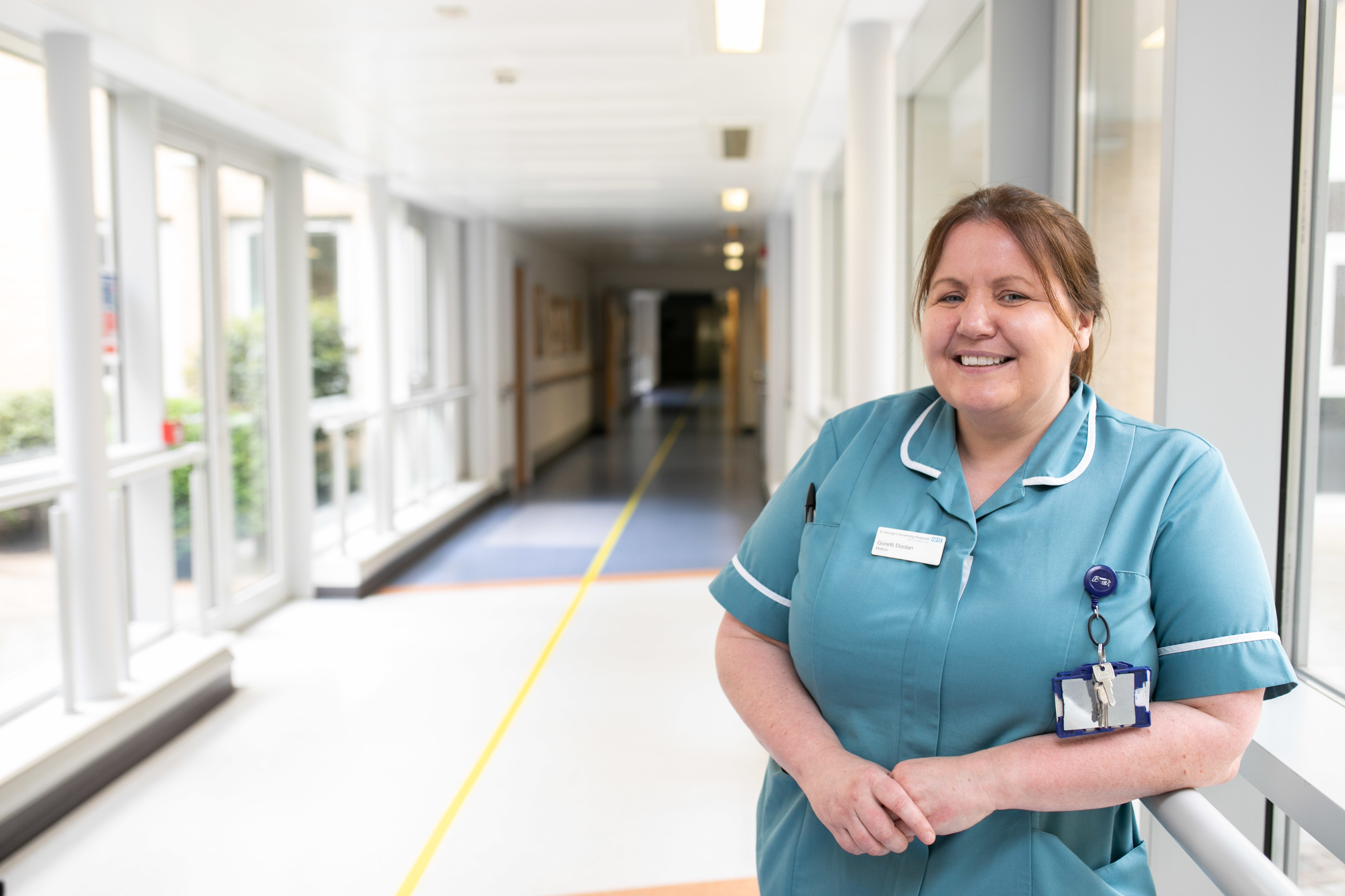 Nurse stood in a hospital smiling at the camera