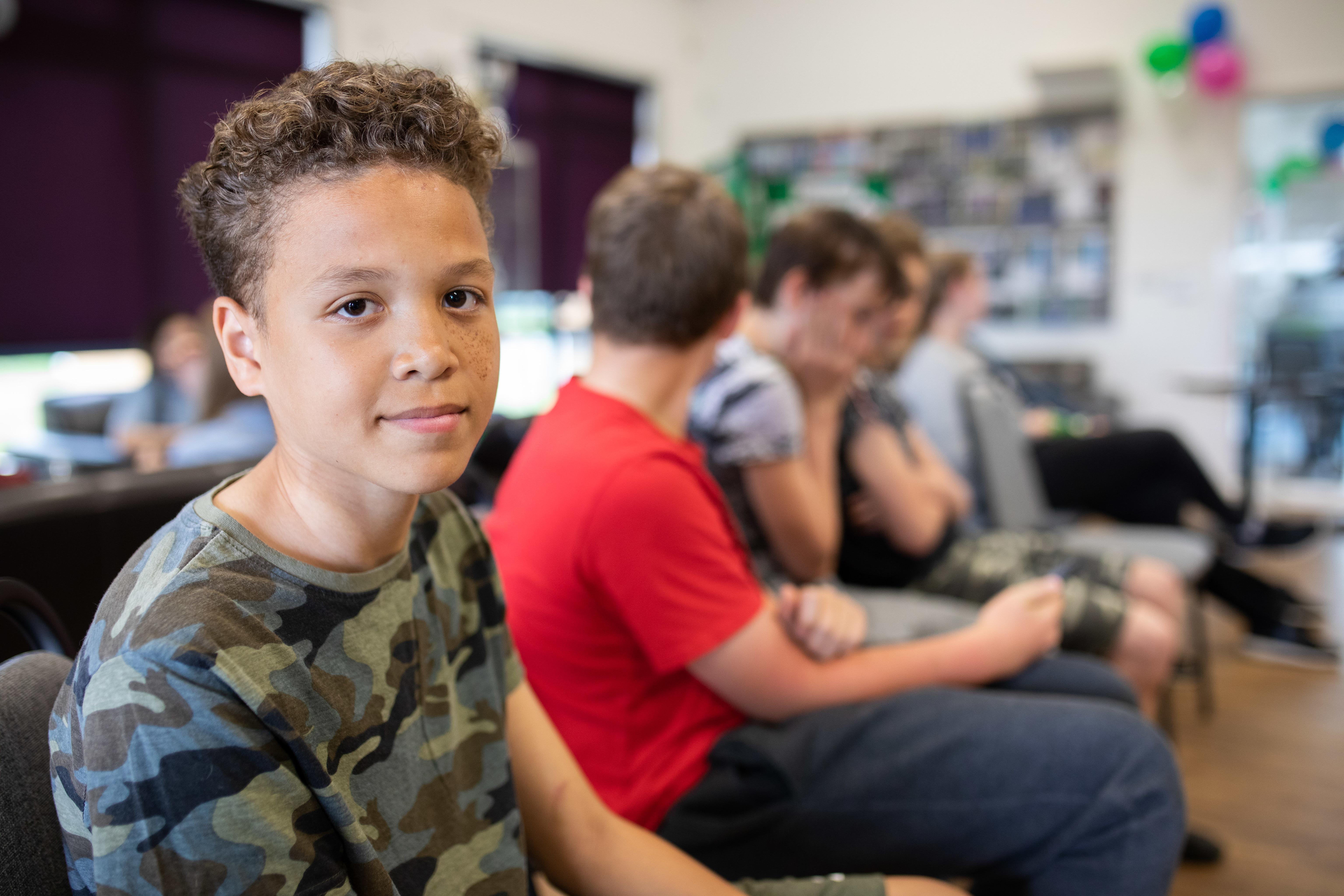 Teenage boy sitting amongst friends
