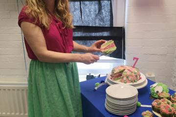 Rebecca cutting Healthwatch's birthday cake