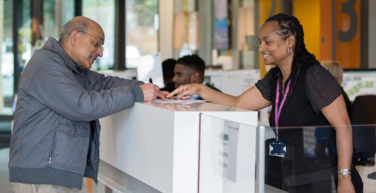 Receptionist helping a man to fill out a form