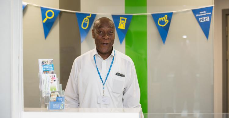 Man in the NHS standing behind a reception desk