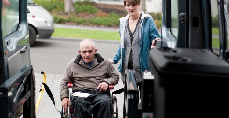 Man in a wheelchair being helped into a bus
