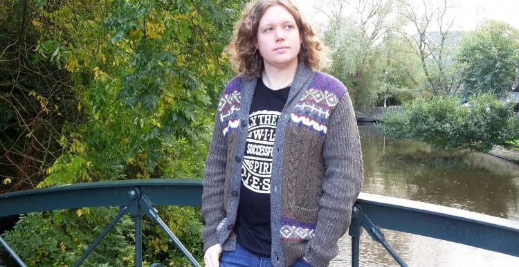 Joe Perkins, a man, standing on a bridge over a body of water