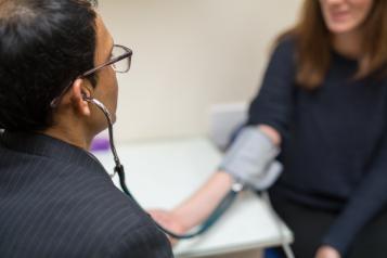 GP taking his patients blood pressure