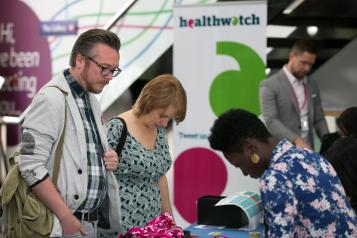 Two people stood looking at a Healthwatch stand at a fair