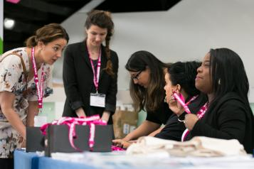 Women in a mentoring scheme having discussions over a table