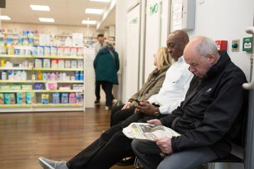 Patients sat waiting in a pharmacy