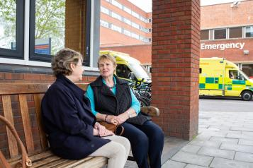 Two women sat talking outside a doctors surgery