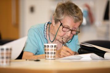 Elderly woman filling in a form