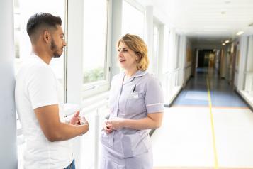 Man talking to nurse in hospital corridor
