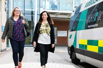 Two women walking into a hospital together