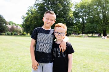 Two young boys standing with their arm round each other