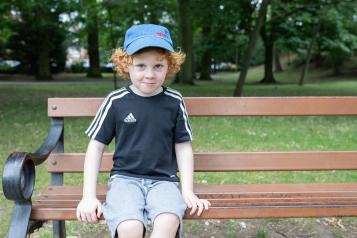 Young boy sitting on a park bench