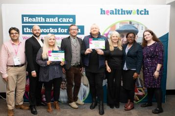 Group in front of Healthwatch posters