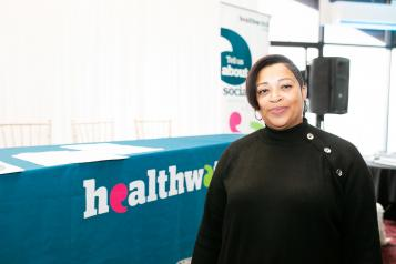 Woman in front of a Healthwatch stand
