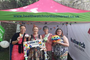 Healthwatch staff standing in front of their stand at the pride event