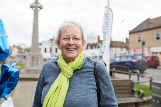 An older white woman next to a Healthwatch banner
