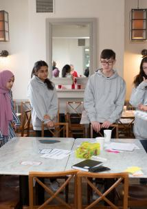 Young people stood around a desk on a workshop