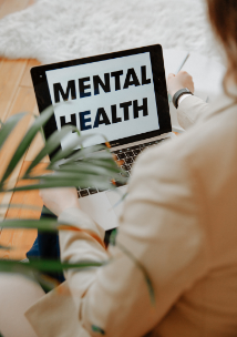 A girl sitting at a laptop. Text on the laptop screen reads: 'mental health'